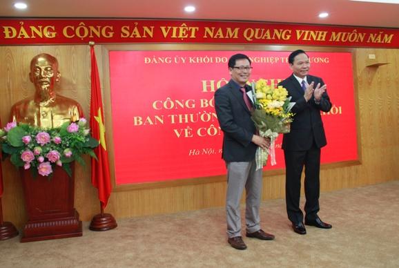 Phó Bí thư Đảng ủy Khối DNTW Lê Văn Châu trao Quyết định và tặng hoa cho đồng chí Chu Đình Động.